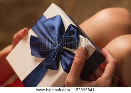 Side view of woman with red dress holding a gift box with blue ribbon on her knees