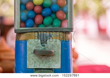 Close-up detail of a capsule vending machine on a colorful blurred out background.