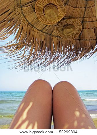 Legs of the woman sunbathing under the sunshade with 2 hats