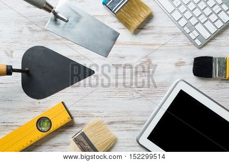 Set of industrial tools and tablet on wooden surface