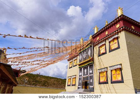 Tibetan Temple brick wall structure and prayer flags in Shangri-la town China with blue sky background