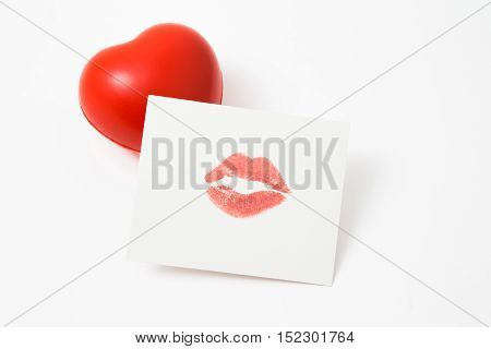 Cute red heart with lipstick kiss on paper sheet isolated