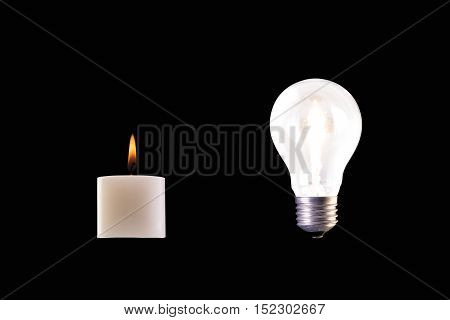 candle and halogen lamp bulb both lighted against black background