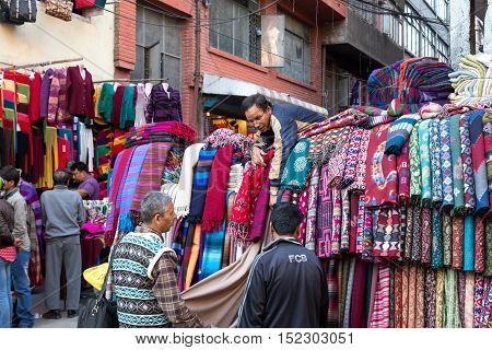 Kathmandu, Nepal - October 19, 2014: A seller showing scarfs to customers on the market in Thamel district