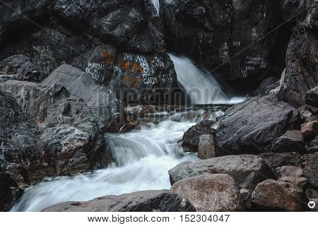 Feed with a water cascade between stones in the mountains