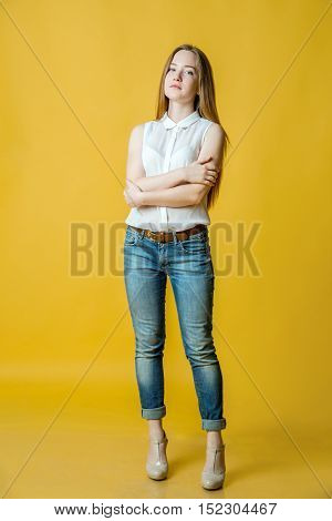 Full length portrait of a smiling woman in casual cloth standing on yellow background