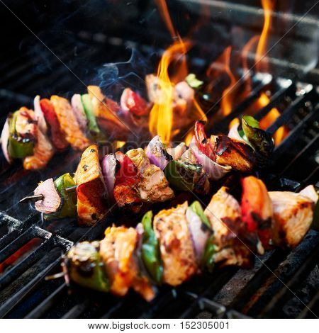 grilling chicken kabobs on flaming grill shot with selective focus