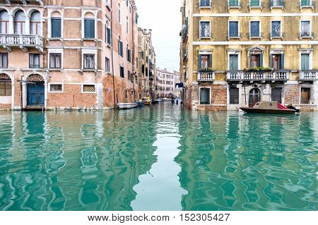 Canals of Venice with boats moored adjacent to buildings