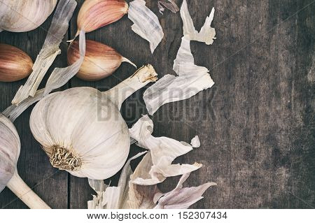 Garlic head and cloves on grey rustic wooden background. Top view with copy space