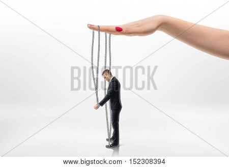 Hand pulling businessman by strings. Puppet. Pull the strings. Weak character. Personnel Management.