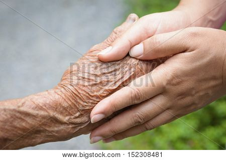 Young boy holding his grandfather hand with love and care