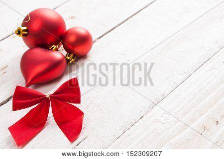 Red Christmas Decorations And Bow On A Wooden Background