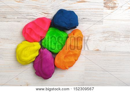 Six colorful lumps of crumpled plasticine put together on a wood surface. Kids activities. DIY ideas. Playing with modeling clay.