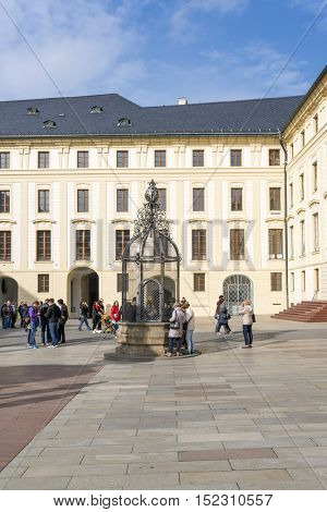 PRAGUE, OCTOBER 15: Tourists in front of a well  and Treasury on the Second Courtyard in Prague Castle  on October 15, 2016 in Prague, Czech Republic.
