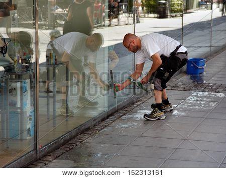 SODERTALJE SWEDEN - July 20 2012: A man cleaning the windows of the shop window to the department store Kringlan in Sodertalje.