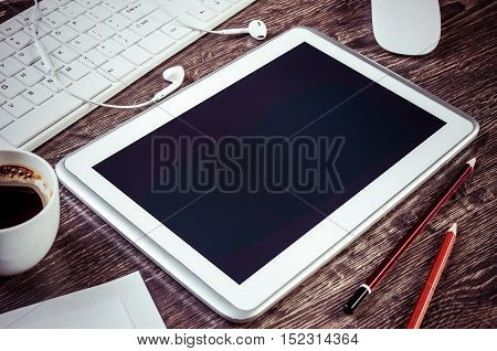 White tablet pc and stationary on wooden table