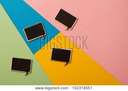 Top view of square chalk board speech bubbles on colored papers metaphor concept for communication