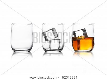 Glasses with whiskey and ice cubes and empty glass with reflection on white background