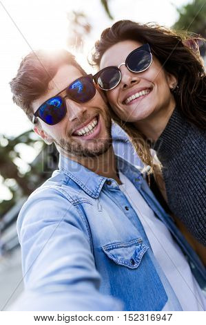 Happy Young Couple Using Mobile Phone In The Street.