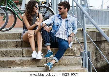 Happy Young Couple Eating Ice Cream In The Street.