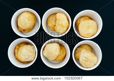 Chicken nuggets in paper cups. Top view against the black table.
