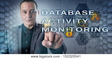 Mature male enterprise data manager is touching DATABASE ACTIVITY MONITORING onscreen. Database security metaphor and information technology concept for continuous database analyzing.
