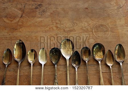 Over head flat lay view of vintage silver spoons side by side on wooden table