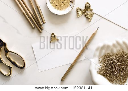 Over head flat lay desk top with gold office supplies and blank notecard for copy or text