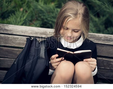Beautiful blond girl in a school uniform sits on a park bench and reading a book. School uniform.Education