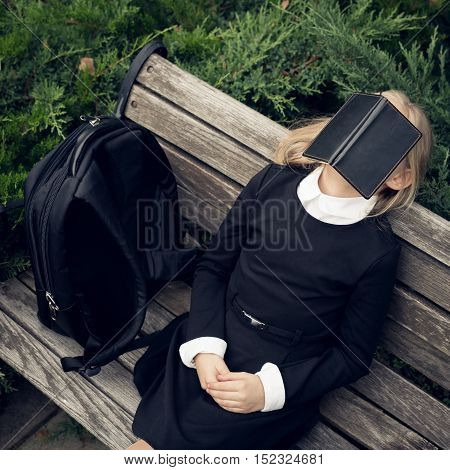 Beautiful blond girl in a school uniform sits on park bench and hiding behind book . Education