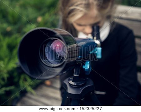 Beautiful blond girl in a school uniform in the park looking through a telescope.Education.