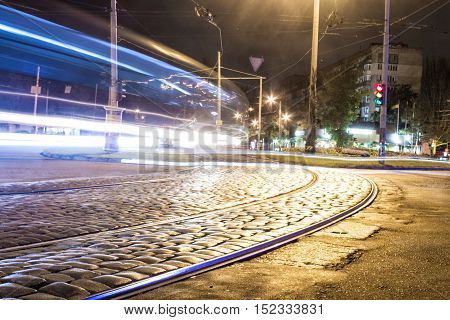 tram track on the pavement at night and moving car with blur light through. The city is on background