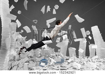 Businessman goes out from a pile of paper sheets
