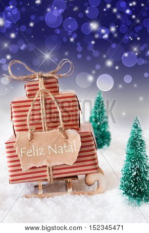Vertical Image Of Sleigh Or Sled With Christmas Gifts Or Presents. Snowy Scenery With Snow And Trees. Blue Sparkling Background With Bokeh. Label With Portuguese Text Feliz Natal Means Merry Christmas