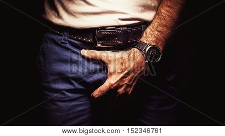 Male person is holding his pant and wearing a watch..