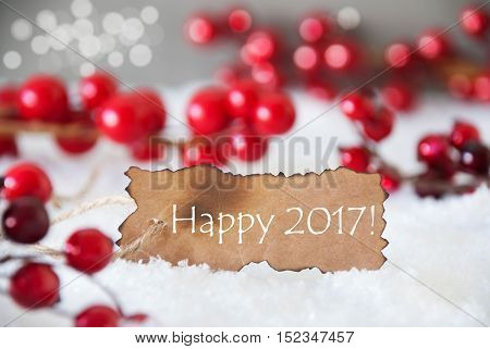 Burnt Label With English Text Happy 2017 For Happy New Year. Red Christmas Decoration On Snow. Cement Wall As Background With Bokeh Effect. Card For Seasons Greetings