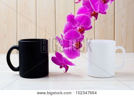 White and black mug mockup with pink orchid. Coffee cup mockup. Empty mug mockup for product presentation. Two coffee mugs.