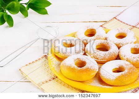 Donuts with caster sugar served on yellow plate. Sweet dessert pastry doughnuts.