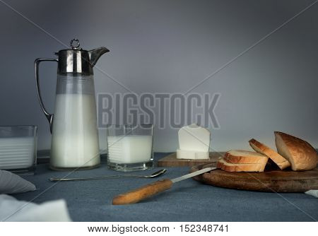 still life. milk jug, candles, tea, eggs, bread rolls cheese on the table