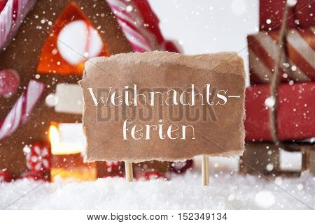 Gingerbread House In Snowy Scenery As Christmas Decoration. Sleigh With Christmas Gifts Or Presents And Snowflakes. Label With German Text Weihnachtsferien Means Christmas Break