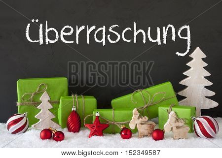 German Text Ueberraschung Means Surprise. Green Gifts Or Presents With Christmas Decoration Like Tree, Moose Or Red Christmas Tree Ball. Black Cement Wall As Background With Snow.