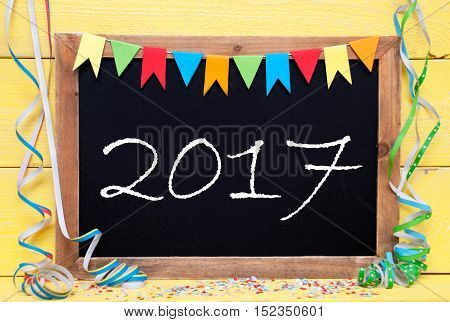 Blackboard With Text 2017 For Happy New Year Greetings. Party Decoration Like Streamer And Confetti. Yellow Wooden Background. Greeting Card For Celebrations