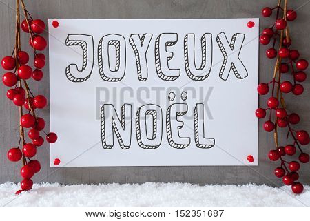 Label With French Text Joyeux Noel Means Merry Christmas. Red Christmas Decoration On Snow. Urban And Modern Cement Wall As Background