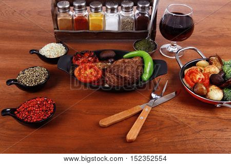 fresh roast beef meat rib eye steak with tomatoes,potatoes, hot chili pepper gern and pink peppercorn saucer, cutlery, set of spice, and red wine glass on light walnut table