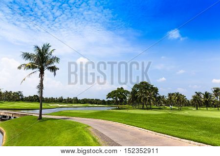 Beautiful view of green golf field with ball and hole at sunrise in the morning. Hobby, leisure and activity concept. Golf ball on lip of cup.