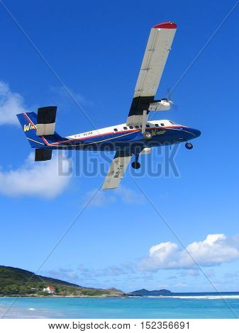 ST. BARTS, FRENCH WEST INDIES - JANUARY 21, 2005: Winair plane taking off from St Barts airport. St. Barts is considered a playground of the rich and famous.