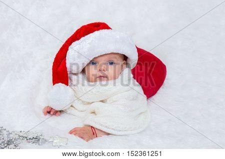 Baby Girl On The Bed Wearing A Santa Hat For Christmas.