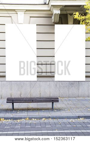 Two blank vertical mockups on a building wall. Autumn street. Front view