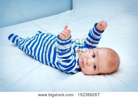 happy little boy lying in the bed. Funny four month old baby in striped sleepsuit at home.