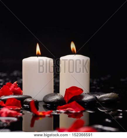 Red rose petals with two white candle and therapy stones